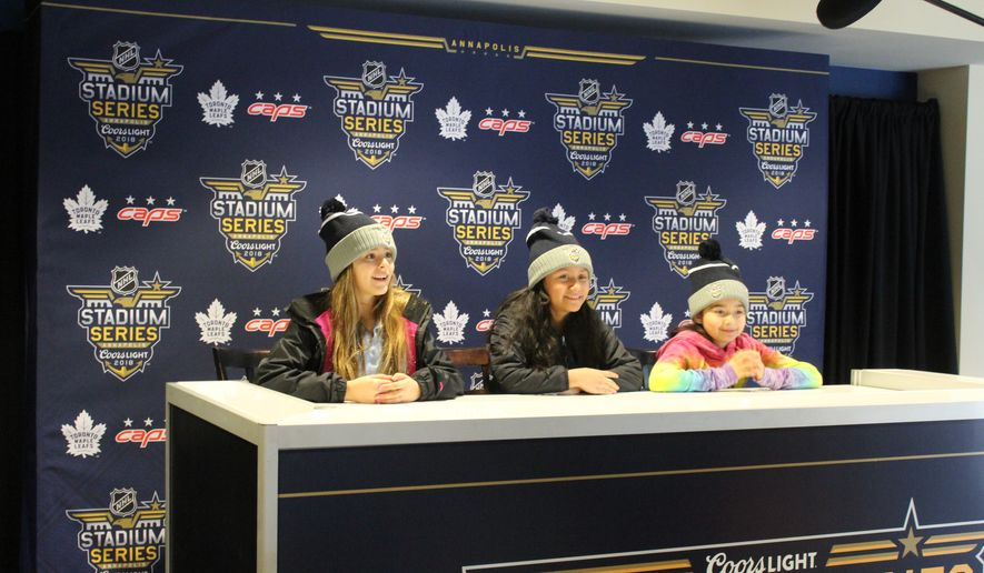 Three students from Germantown Elementary School in Annapolis, Maryland pose for photos in the interview room at Navy-Marine Corps Memorial Stadium on March 1, 2018. The stadium is set up for the NHL Stadium Series game March 3 between the Washington Capitals and the Toronto Maple Leafs. (Adam Zielonka / The Washington Times)