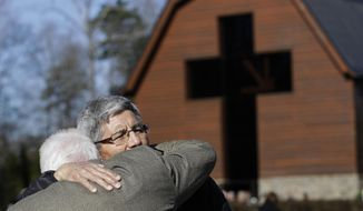 Edgar Valenzuela, right, hugs Clyde Fonderin, left, after they paid their respects to Rev. Billy Graham during a public viewing at the Billy Graham Library in Charlotte, N.C., Tuesday, Feb. 27, 2018. (AP Photo/Chuck Burton)