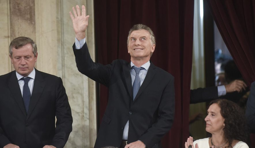 Argentina's President Mauricio Macri waves as he arrives to open the 2018 session of Congress and give the annual State of the Nation address, flanked by Emilio Monzo, president of the Chamber of Deputies, left, and Vice President Gabriela Michetti, in Buenos Aires, Argentina, Thursday, March 1, 2018. (AP Photo/Pablo Stefanec)