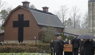 Pallbearers carry the casket of the Rev. Billy Graham past family members as it returns to the Billy Graham Library in Charlotte, N.C., Thursday, March 1, 2018. His funeral will be Friday. (AP Photo/Chuck Burton)