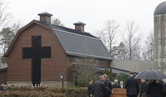 In this file photo, pallbearers carry the casket of the Rev. Billy Graham past family members as it returns to the Billy Graham Library in Charlotte, N.C., Thursday, March 1, 2018.  (AP Photo/Chuck Burton) **FILE**