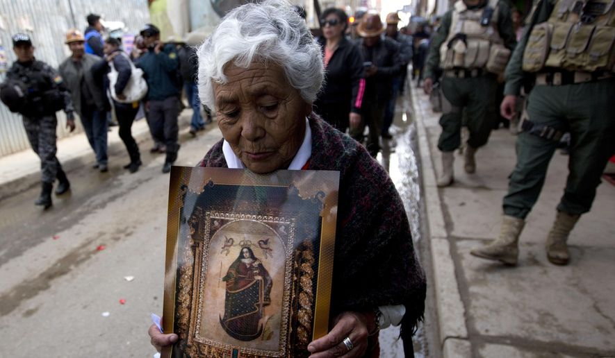 A woman holds an image of Our Lady of Socavon, in a procession honoring their patron saint, in Oruro, Bolivia, Thursday, March 1, 2018. Hundreds, including Oruro's archbishop, governor and mayor, marched in protest of a Bolivian artist and her painting that depicts the religious icon wearing red lingerie and transparent stockings. The governor gave state workers the day off in order to participate in the demonstration. (AP Photo/Juan Karita)