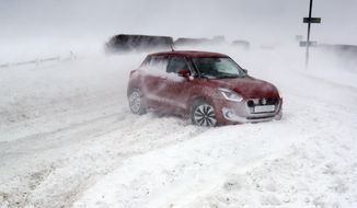 Cars in snowy conditions on the A192 road near Blyth, north east England, Thursday March 1, 2018. Persistent snow and freezing conditions are causing delays in many parts of Britain, with roads and train service hit particularly hard. Emergency officials said many drivers had to be rescued from stranded vehicles. (Owen Humphreys/PA via AP)