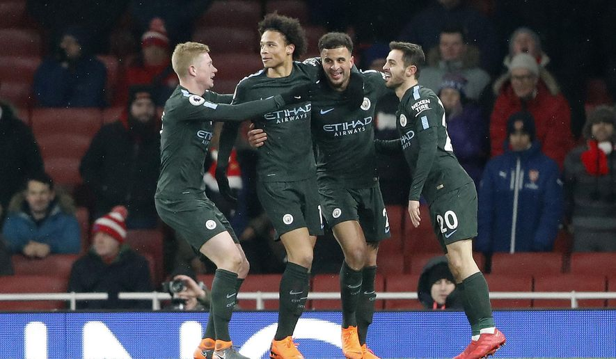 Manchester City's Leroy Sane, second left, celebrates with teammates after scoring his side's third goal during the English Premier League soccer match between Arsenal and Manchester City at the Emirates stadium in London, Thursday, March 1, 2018.(AP Photo/Frank Augstein)