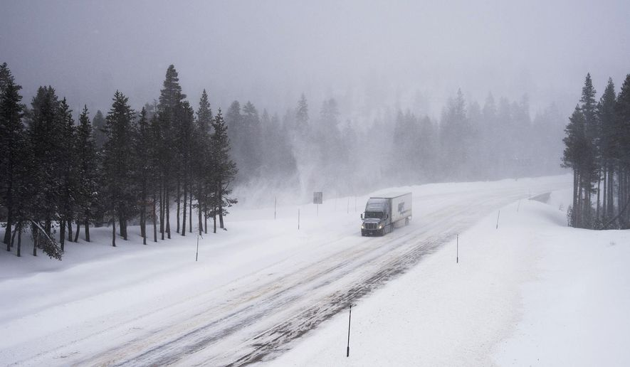 A truck heads west through the snow on Interstate 80, Thursday, March 1, 2018, near Donner Summit, Calif. A major winter storm swept south through California on Thursday, bringing heavy snow and strong winds to mountains and steady rain elsewhere, while prompting mandatory evacuations for coastal areas to the south that were devastated by deadly mudslides in January. The California Department of Transportation said 90-miles stretch of Interstate 80 was closed between Colfax, California, and the Nevada state line due to whiteout conditions.(Randy Pench/The Sacramento Bee via AP)