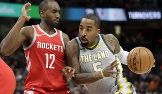 FILE - In this Feb. 3, 2018, file photo, Cleveland Cavaliers' J.R. Smith (5) drives past Houston Rockets' Luc Mbah a Moute (12), from Cameroon, in the first half of an NBA basketball game in Cleveland. Smith has been suspended one game by the team for detrimental conduct. The team gave no further specifics about the punishment. Smith will serve the penalty on Thursday, March 1, 2018, night as the Cavs host the Philadelphia 76ers. (AP Photo/Tony Dejak, File)