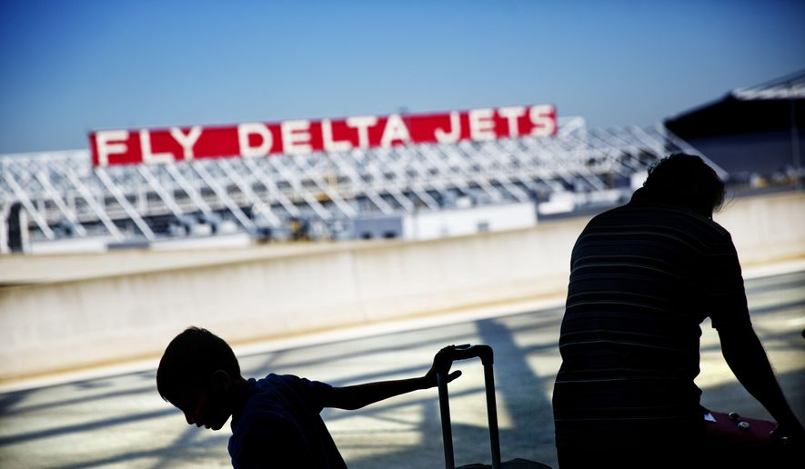 In this Oct. 13, 2016, file photo, passengers unload in front of a Delta Air Lines sign at Hartsfield-Jackson Atlanta International Airport, in Atlanta. (AP Photo/David Goldman, File)