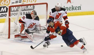 Florida Panthers center Vincent Trocheck (21) can't score as New Jersey Devils goaltender Cory Schneider (35) and Sami Vatanen (45) defend during the second period of an NHL hockey game, Thursday, March 1, 2018, in Sunrise, Fla. (AP Photo/Joe Skipper)