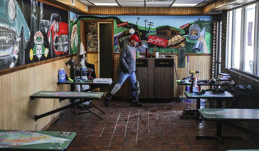 "In this Feb. 12, 2018 photo, contractor Tim Lesak walks past a mural while working at the  Launching Pad Drive-In in Wilmington, Ill. Since October 2017, Holly Barker and Tully Garrett have been repairing the old restaurant. It had been shut down for six years and falling into disrepair until Barker and Garrett came upon it during an antiquing excursion to Wilmington. ""We thought we were buying a restaurant, and it turned out we were buying much, much more,"" Garrett said, as he talked about what the restaurant means to them and the people of Wilmington who are eager to see it reopen. (Eric Ginnard /Herald-News via AP)"