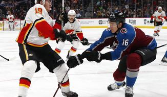 Colorado Avalanche defenseman Nikita Zadorov, right, hits Calgary Flames left wing Matthew Tkachuk as Tkachuk drives to the net with the puck during the second period of an NHL hockey game Wednesday, Feb. 28, 2018, in Denver. (AP Photo/David Zalubowski)