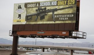 """This Thursday, March 1, 2018 shows a vandalized billboard near Interstate 15 in Las Vegas. The advertisement inviting tourists to fire an assault-style rifle, which originally said """"Shoot a .50 caliber only $29,"""" was changed to say, """"Shoot A School Kid Only $29."""" (Bizuayehu Tesfaye/Las Vegas Review-Journal via AP)"""