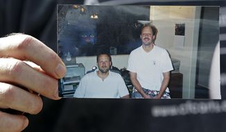 FILE - In this Oct. 2, 2017 file photo, Eric Paddock holds a photo of himself, at left, and his brother, Las Vegas shooter Stephen Paddock, at right, outside his home in Orlando, Fla. A Nevada judge on Thursday, March 1, 2018 named a forensic finance officer to tally the assets left by Stephen Paddock, who killed himself after unleashing the deadliest mass shooting in modern U.S. history on the Las Vegas Strip. Eric Paddock wants the assets distributed to victims. (AP Photo/John Raoux, File)