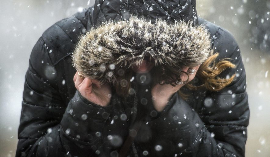 Flint resident Sarah Elkins covers her head from the heavy snowfall as she crosses Saginaw Street on Thursday, March 1, 2018 in Flint, Mich. (Jake May/The Flint Journal-MLive.com via AP)