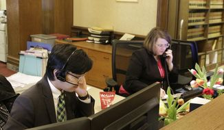 Kento Azegami, left, and Jeanne Blackburn answer phones at the front desk at Gov. Jay Inslee's office in Olympia, Wash., on Thursday, March 1, 2018. Inslee's office has been receiving thousands of emails and phone calls asking him to veto a bill passed hastily by the Washington Legislature last week that would circumvent a recent court ruling that found state lawmakers are fully subject to the state's Public Records Act. (AP Photo/Rachel La Corte)