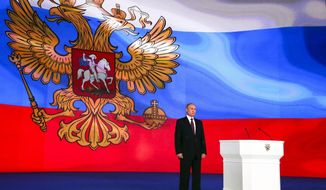 Russian President Vladimir Putin stands after giving his annual state of the nation address in Manezh in Moscow, Russia, Thursday, March 1, 2018. Putin set a slew of ambitious economic goals, vowing to boost living standards, improve health care and education and build modern infrastructure in a state-of-the-nation address. (Mikhail Klimentyev, Sputnik, Kremlin Pool Photo via AP)