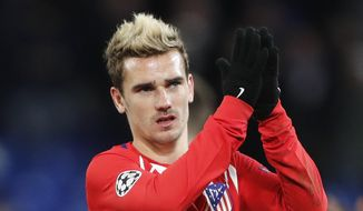 FILE - In this Tuesday, Dec. 5, 2017 file photo, Atletico's Antoine Griezmann greets fans after their 1-1 draw in the Champions League Group C soccer match againt Chelsea at Stamford Bridge stadium in London. Antoine Griezmann is giving Atletico Madrid fans hope that a late run for the Spanish league title is still possible. Griezmann will enter their game on Sunday, March 4, 2018 against Barcelona boosted by two outstanding performances in the last two league rounds. He had a hat trick against Sevilla and scored four goals against Leganes. (AP Photo/Frank Augstein, File)