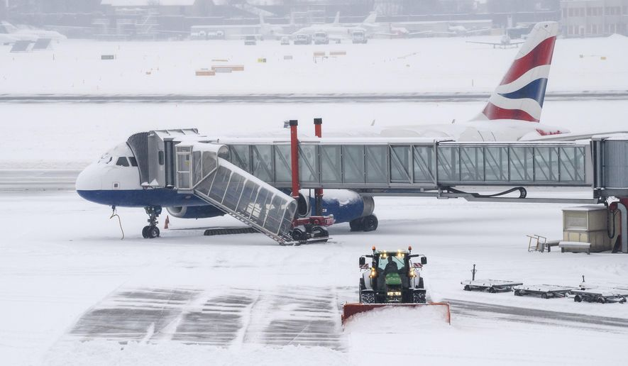The fire brigade of Airport Security Services (SSA) ride a snowplow removing snow on the runway at the Geneva Airport, in Geneva, Switzerland, Thursday, March 1, 2018. (Martial Trezzini/Keystone via AP)