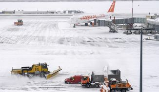 """The fire brigade of Airport Security Services (SSA) rides  snowplows removing snow on the runway during  at the Geneva Airport, in Geneva, Switzerland, Thursday, March 1, 2018. Geneva's airport has been closed """"until further notice"""" after the Swiss city was blanketed by snowfall overnight. (Martial Trezzini/Keystone via AP)"""