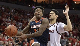 Virginia guard Nigel Johnson (23) goes in for a layup past the defense of Louisville forward Anas Mahmoud (14) during the first half of an NCAA college basketball game, Thursday, March 1, 2018, in Louisville, Ky. (AP Photo/Timothy D. Easley) ** FILE **