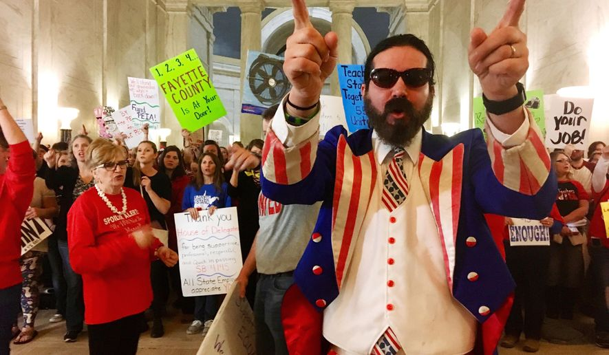 Parry Casto, a fifth grade teacher at the Explorer Academy in Huntington, W.Va., dressed in an Uncle Sam costume leads hundreds of teachers in chants outside the state Senate chambers at the Capitol in Charleston, W.Va., Thursday, March 1, 2018. Teachers were awaiting a Senate vote on a proposed 5 percent pay increase for them. (AP Photo/John Raby)
