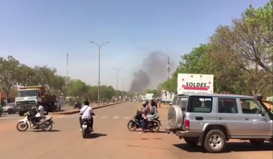 Smoke rises in the background in Ouagadougou, Burkina Faso, in this image taken from video Friday March 2, 2018.  Gunfire and explosions rocked Burkina Fasos capital early Friday in what the police said was a suspected attack by Islamic extremists. By midday the gunfire became intermittent and helicopters flew above the French Embassy in Ouagadougou.(AP Photo)