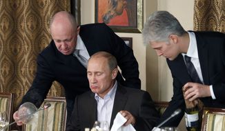 FILE - In this Friday, Nov. 11, 2011 file photo, businessman Yevgeny Prigozhin, left, serves food to Russian Prime Minister Vladimir Putin, center, during dinner at Prigozhin's restaurant outside Moscow, Russia. U.S. indictment charged 13 Russians with running a hidden social media trolling campaign in a bid to disrupt the 2016 U.S. presidential election. (AP Photo/Misha Japaridze, Pool, File) **FILE**