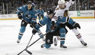 San Jose Sharks' Joonas Donskoi, center, is defended by Chicago Blackhawks' Carl Dahlstrom during the second period of an NHL hockey game Thursday, March 1, 2018, in San Jose, Calif. (AP Photo/Marcio Jose Sanchez)