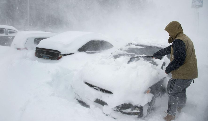 Heavy winds blow snow as Ryan Foster, 25, scrapes snow from his car in the parking lot where he lives at the Donner Summit Lodge in Norden on Thursday, March 1, 2018, near Donner Summit, Calif. A major winter storm swept south through California on Thursday, bringing heavy snow and strong winds to mountains and steady rain elsewhere, while prompting mandatory evacuations for coastal areas to the south that were devastated by deadly mudslides in January. (Randy Pench/The Sacramento Bee via AP)