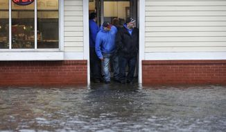 People stand at the entrance to a pizza shop as water floods a street, in Scituate, Mass., Friday, March 2, 2018. A major nor'easter pounded the East Coast on Friday, packing heavy rain and strong winds as residents from the mid-Atlantic to Maine braced for coastal flooding. (AP Photo/Steven Senne)