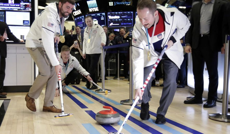 U.S. Olympic gold medalists in curling John Landsteiner, Matt Hamilton, Joe Polo and Tyler George, left to right, demonstrate their sport on the floor of the New York Stock Exchange, before ringing the opening bell, Friday, March 2, 2018. (AP Photo/Richard Drew)