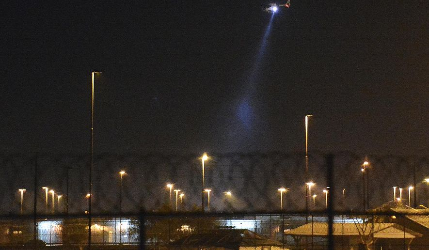 In this Thursday, March 1, 2018 photo, a helicopter circles the Arizona State Prison Complex-Yuma in San Luis, Ariz. Inmates at the Arizona prison threw rocks, set fire to mattresses and attacked guards. (Randy Hoeft/Yuma Sun  /The Yuma Sun via AP)
