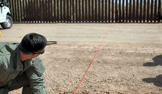 FILE--In this April 14, 2016, file photo provided by U.S. Customs and Border Protection, a Border Patrol agent shows the path of a tunnel that crosses the U.S.-Mexico border near Calexico, Calif. The federal government has started work on a border wall in California to replace a decades-old decaying barrier. SWF Constructors, a tiny Nebraska startup, was awarded the first border wall construction project under President Donald Trump. It is the offshoot of a construction firm that was accused in a government audit of shady billing practices. (U.S. Customs and Border Protection via AP, file)