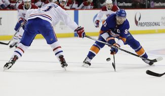 New York Islanders' John Tavares (91) and Montreal Canadiens' David Schlemko (21) reach for the puck during the second period of an NHL hockey game Friday, March 2, 2018, in New York. (AP Photo/Frank Franklin II)