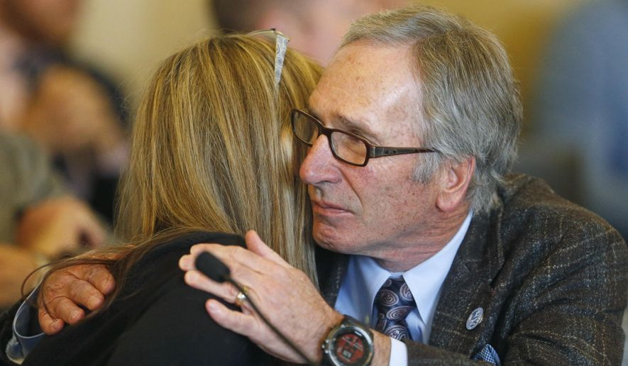 Republican Rep. Gage Froerer hugs Christine Stenquist after testifying during a hearing Wednesday, Feb. 21, 2018, at the Utah State Capitol, in Salt Lake City. A Republican state lawmaker plan to repeal the death penalty in deep-red Utah cleared its first test Wednesday, winning approval from a legislative committee as Utah's GOP governor said he's open to signing the ban. Stenquist relayed her personal experience with the brutal murder of her sister and the family's decision not to pursue the death penalty. (AP Photo/Rick Bowmer)