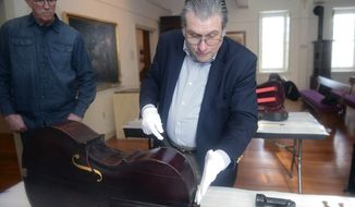 In this Feb. 6, 2018 photo, a cello, built by John Antes, a Moravian Missionary, purchased by Tom Riddle is examined for authenticity at the Moravian Historical Society by Phillip J. Kass in Nazareth, Pa. It is thought that the cello is among the first bowstring instruments made in America. A violin and viola where also examined as all three are thought to have been made by Antes. (Amy Herzog/The Morning Call via AP)