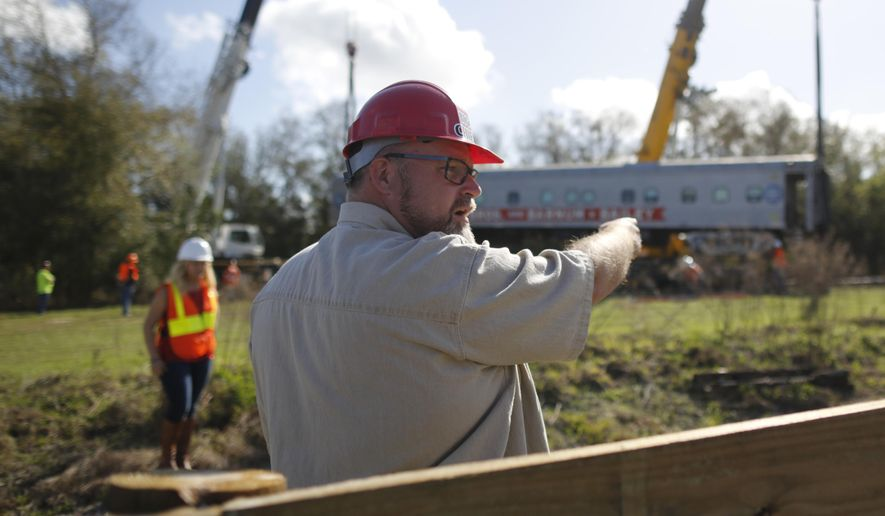 "In this Saturday, Feb. 23, 2018 photo, Daryl Kirby, founder of Kirby Family Farm, oversees operations during the installment of 16 unit trains on 2,000 feet of newly laid train tracks in Williston, Fla.. The Ringling Brothers Circus train was the most recognized privately owned train in the world and ofter referred to as ""the city without a zip code."" [Jessica Rodriguez/Star-Banner via AP)"