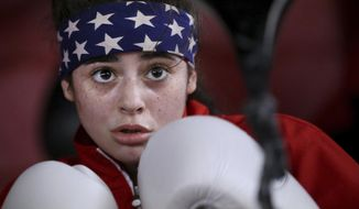 In this Feb. 7, 2018 photo, Natalie Dove prepares to punch a double-end bag as she works out at Philly's Next Champ boxing gym in Philadelphia. Just 16, Dove is a three-time winner of the prestigious National Women's Golden Gloves. In 2016, she fought her way onto Team USA with a second-place finish at the USA Boxing National Championships. Last year, Team USA ranked her the nation's No. 1 amateur junior woman boxer in her weight class. (Tim Tai/The Philadelphia Inquirer via AP)