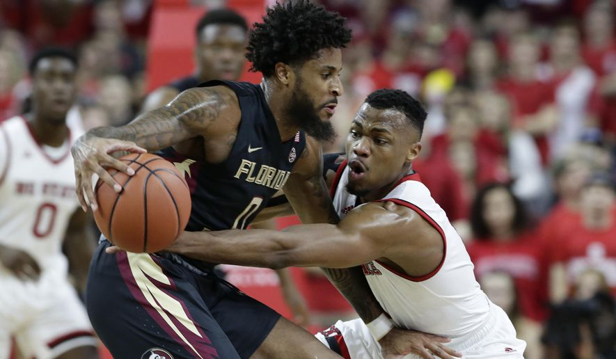 FILE- In this Feb. 25, 2018, file photo, Florida State's Phil Cofer (0) dribbles at North Carolina State's Torin Dorn defends during the first half of an NCAA college basketball game in Raleigh, N.C. Florida State Phil Cofer is hoping that Saturday's game won't be his final home game. The senior forward, who is one of the most improved players in the Atlantic Coast Conference this season, has petitioned the NCAA for a fifth season after a foot injury mostly wiped out his sophomore season. (AP Photo/Gerry Broome. File)