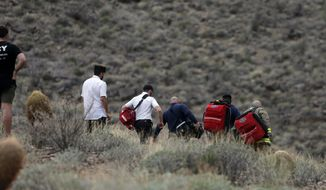 FILE - In this Saturday, Feb. 10, 2018, file photo, emergency personnel arrive at the scene of a deadly tour helicopter crash along the jagged rocks of the Grand Canyon, in Arizona. The parents of a British tourist who died after the crash have filed a lawsuit. (Teddy Fujimoto via AP, File)