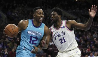 Charlotte Hornets' Dwight Howard, left, drives to the basket as Philadelphia 76ers' Joel Embiid defends during the first half of an NBA basketball game Friday, March 2, 2018, in Philadelphia. (AP Photo/Chris Szagola)