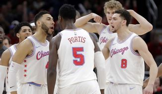 The Chicago Bulls gather around Bobby Portis (5) after he made a clutch shot during the second half of an NBA basketball game against the Dallas Mavericks, Friday, March 2, 2018, in Chicago. (AP Photo/Charles Rex Arbogast)