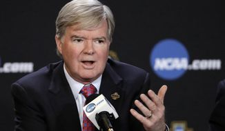 FILE - In this March 30, 2017, file photo, NCAA President Mark Emmert answers a question at a news conference in Glendale, Ariz. Emmert is hopeful the scandal roiling college basketball will lead to major rule changes, but schools paying players is likely a nonstarter. In a 45-minute phone interview with The Associated Press, Emmert said he expects a commission to reform college basketball to put forth proposals that could modernize NCAA rules on player-agent relationships, address the NBAs one-and-done rule and devise new ways to handle contentious and high-profile enforcement cases. (AP Photo/David J. Phillip, File)