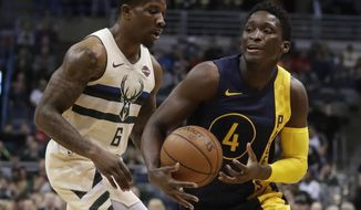 CORRECTS DAY AND DATE - Indiana Pacers' Victor Oladipo is fouled as he drives past Milwaukee Bucks' Eric Bledsoe during the first half of an NBA basketball game Friday, March 2, 2018, in Milwaukee. (AP Photo/Morry Gash)