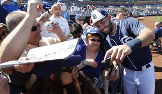 San Diego Padres' Eric Hosmer, right, poses for a photo with a fan before a spring training baseball game against the Kansas City Royals, Friday, March 2, 2018, in Peoria, Ariz. (AP Photo/Charlie Neibergall)