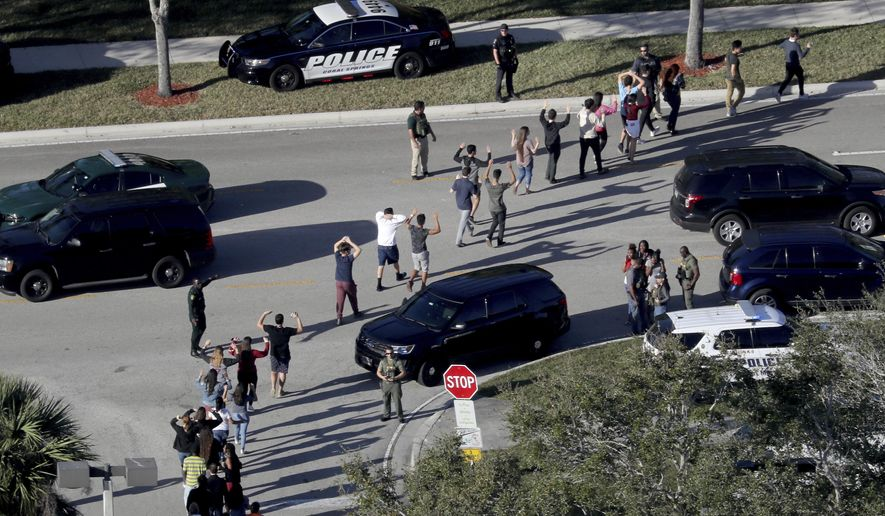 FILE - In this Feb. 14, 2018 file photo,  students hold their hands in the air as they are evacuated by police from Marjory Stoneman Douglas High School in Parkland, Fla., after a shooter opened fire on the campus. A sheriff's office captain told deputies to form a perimeter instead of confronting the gunman at the high school where several people were killed in a mass shooting, according to documents obtained by the Miami Herald. The newspaper reported late Thursday, March 1,  that it had obtained a partial Broward Sheriff's Office dispatch log, which showed that Capt. Jan Jordan gave the order for deputies to establish a perimeter. (Mike Stocker/South Florida Sun-Sentinel via AP)