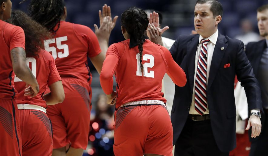 Mississippi head coach Matt Insell, right, slaps hands with his players during a timeout in the first half of an NCAA college basketball game against Florida at the women's Southeastern Conference tournament, Wednesday, Feb. 28, 2018, in Nashville, Tenn. (AP Photo/Mark Humphrey)