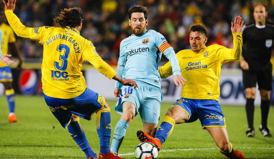 FC Barcelona's Lionel Messi, center, duels against Las Palmas' Matias Aguirregaray, left, and Ximo Navarro, during a Spanish La liga soccer match at the Gran Canaria stadium in the Canary island of Las Palmas, Thursday March 1, 2018. (AP Photo/Lucas de Leon)