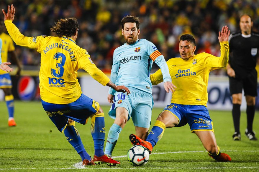FC Barcelona's Lionel Messi, center, duels against Las Palmas' Matias Aguirregaray, left, and Ximo Navarro, during a Spanish La liga soccer match at the Gran Canaria stadium in the Canary island of Las Palmas, Thursday March 1, 2018. (AP Photo/Lucas de Leon)