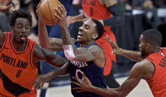 Minnesota Timberwolves guard Jeff Teague, center, drives to the basket past Portland Trail Blazers forwards Maurice Harkless, right, and Al-Farouq Aminu, left, during the first half of an NBA basketball game in Portland, Ore., Thursday, March 1, 2018. (AP Photo/Craig Mitchelldyer)