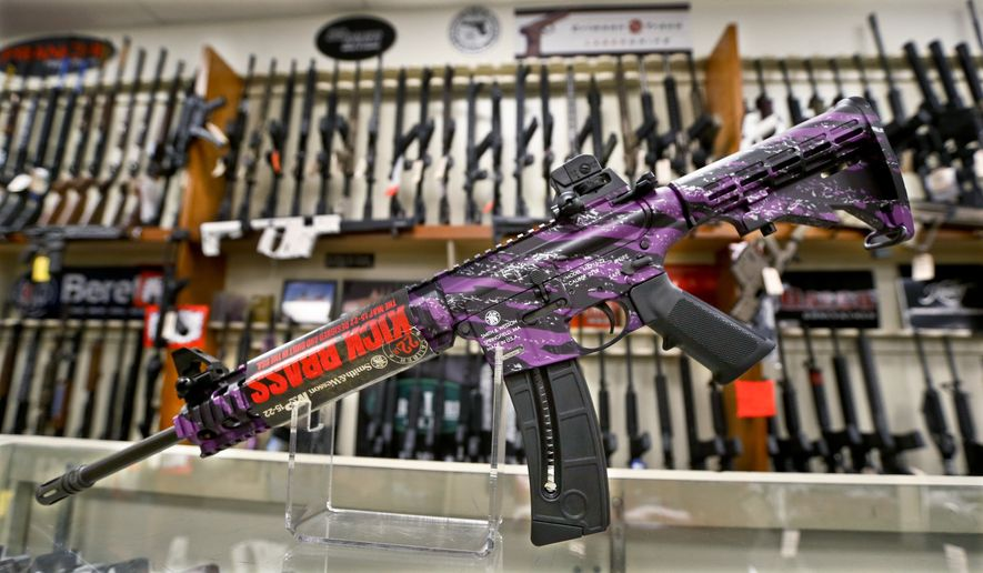 A Smith & Wesson M&P 15-22 Muddy Girl Sport rifle chambered in .22 LR is shown in front of a rack of other rifles at Duke's Sport Shop in New Castle, Pa. on Thursday, March 1, 2018. Sales of firearms slowed dramatically after the election of President Donald Trump in 2016. American Outdoor Brands, which owns Smith & Wesson, said revenue fell by one-third over the past three months. The company said demand dropped in December and January, before the shootings in Parkland, Florida, and the debates on gun laws that followed. The company doesn't expect sales to improve much over the next 18 months. (AP Photo/Keith Srakocic)